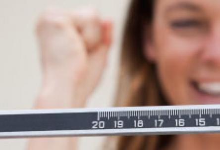 Photo: Woman on a scale excited about weight loss results