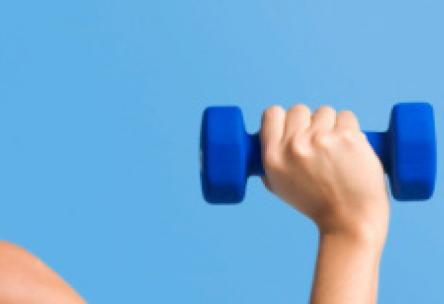 Photo: Fit woman pushing dumbbell over head