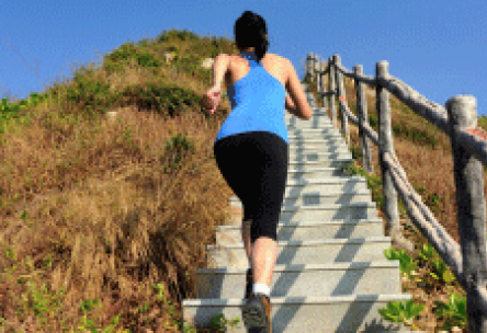 Photo: Fit woman running up a long set of outdoor stairs on a mountain