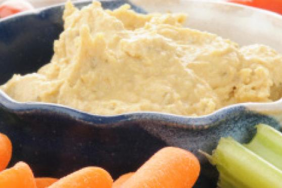 Photo: Bowl of hummus surrounded by crackers and vegetables