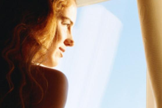 Photo: Young woman staring out a window during sunrise