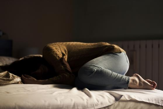 Depressed woman curled up on a bed