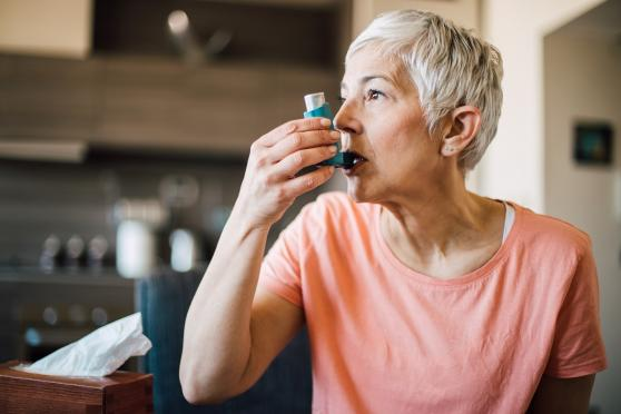 Older woman using asthma inhaler