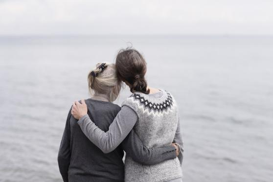 Mother and daughter embracing each other, looking at the ocean