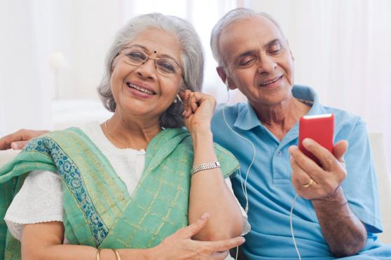 Photo: Mature couple wearing headphones and listening to something on their smartphone.