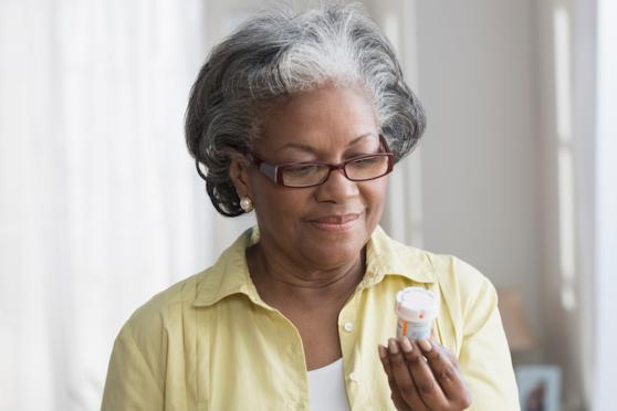 older woman looking at medication