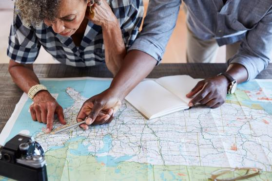 Photo: Woman and man looking at a road map and planning a trip.