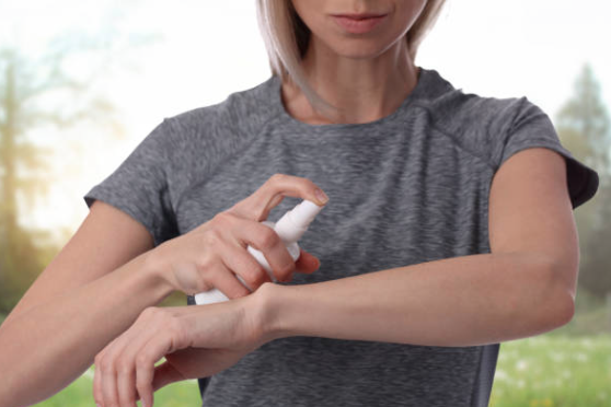 woman spraying bug repellent on arm